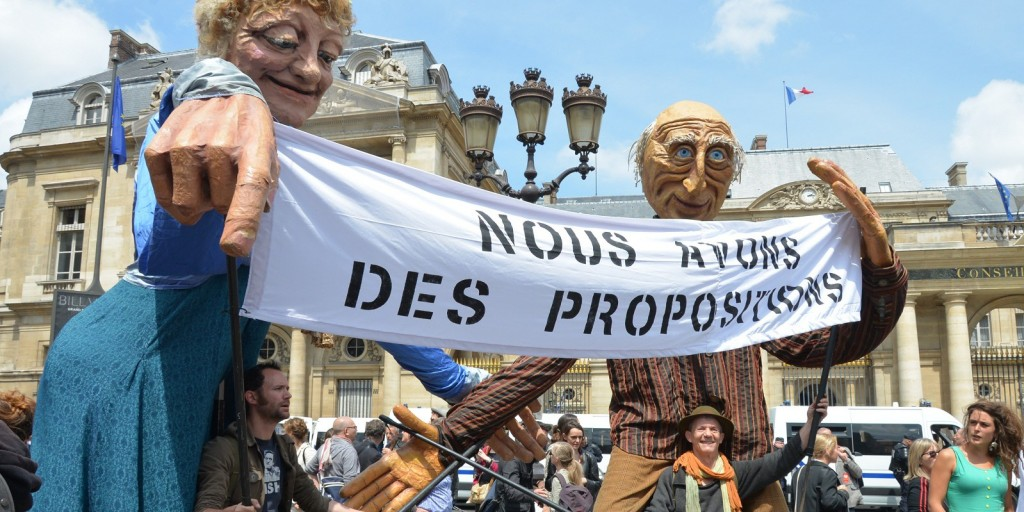FRANCE, Paris : Giant puppets hold a sign reading We have propositions as protestors take part in a demonstration called by French artists and entertainment workers, known as intermittents du spectacle, on June 16, 2014 in front of Le Louvre museum in Paris, in protest against the French government's plan to reform their status. CITIZENSIDE/CLAUDE SZMULEWICZ